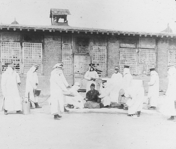 A medical team in protective clothing examine a man suspected of having the plague